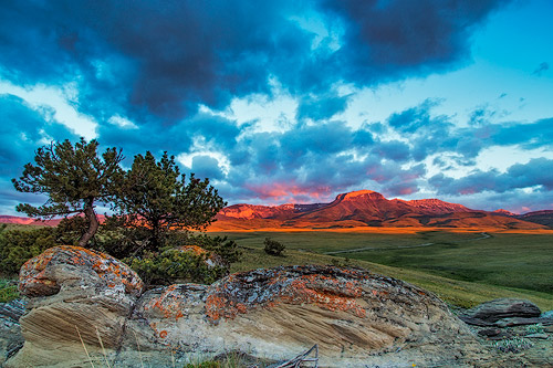 Fiery sunrise light strikes Ear Mountain along the Rocky Mountain Front near Choteau, Montana.